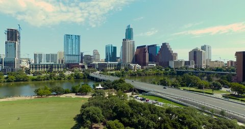 The camera starts at a low altitude but gains height as it approaches the Austin, Texas skyline on a bright beautiful day.  Traffic and pedestrians populate the streets and sidewalks.