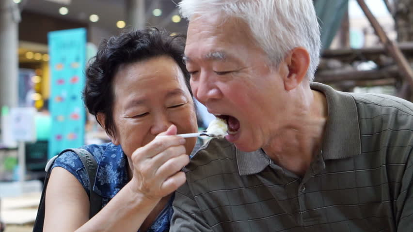 Asian senior elder couple eating an ice cream and feed each other abstract eternal love