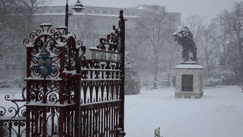 Winter Christmas Snow in the urban park: gates and Lion statue, England, Europe