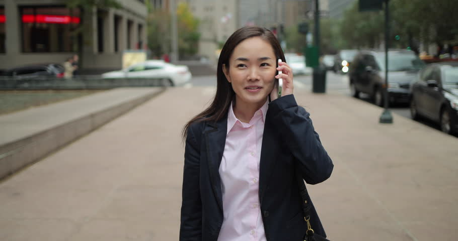 Asian business woman in New York City walking  talking on cell phone | Shutterstock HD Video #12764873