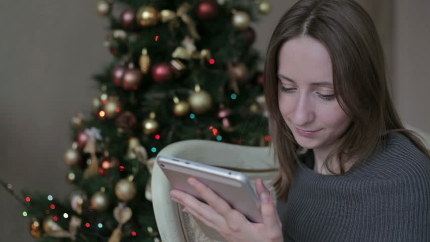 Happy woman looking in tablet PC in front of Christmas tree | Shutterstock HD Video #12765749