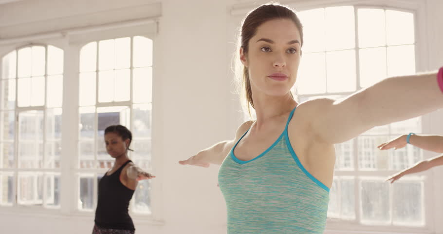 Yoga class multi racial group of women exercising healthy lifestyle in fitness studio yoga warrior poses #12794969