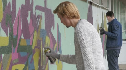 Two male graffiti painters spraying graffiti on wall. Street art performance,raw video,no grading. Talented urban artists painting mural. Young men drawing graffiti on wall with sprays. Street art.