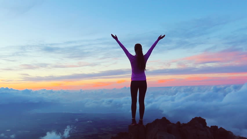 Reaching The Top. Happy successful fitness woman raising arms to the sky at sunset. Success | Shutterstock HD Video #12816758