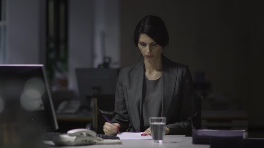 Women as business leaders. Woman In Business Suit. Sitting in an office at her desk working late, Paperwork. | Shutterstock HD Video #12824561