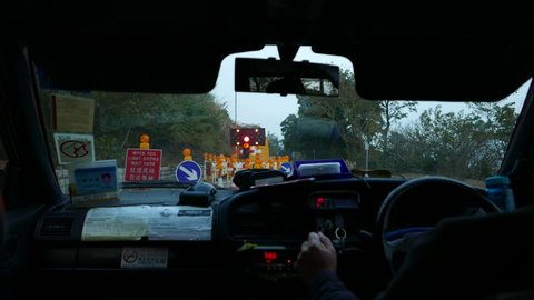 HONG KONG - FEBRUARY 03, 2015: Making detour of the narrow road part due to construction ahead. Shoot from backsit of taxi car, look forward. Evening time, rural road along Lantau Island.