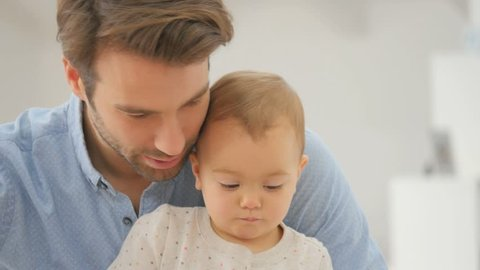 Closeup of man with baby looking at digital tablet