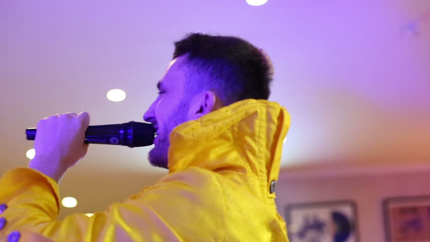 Showman in yellow fashionable suit speaks in a microphone. Attractive presenter conducts glamorous party. Emotions, expression and energy of a leading of an event. Closeup.