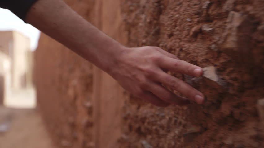 Man walks and grazes hand on stone wall. Shot in Morocco. Royalty-Free Stock Footage #12874283