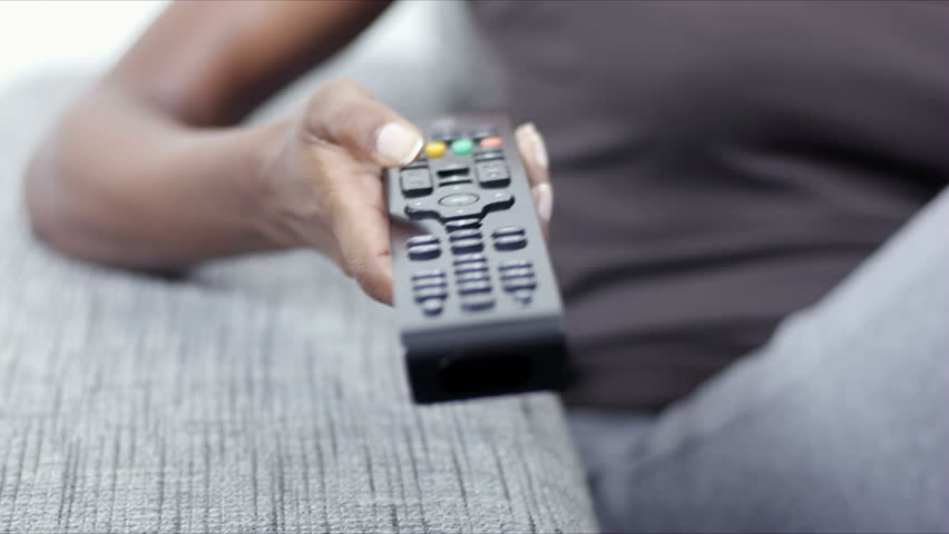 Mid adult Indian woman on sofa, changing tv channel with remote control while eating carrot | Shutterstock HD Video #1287757