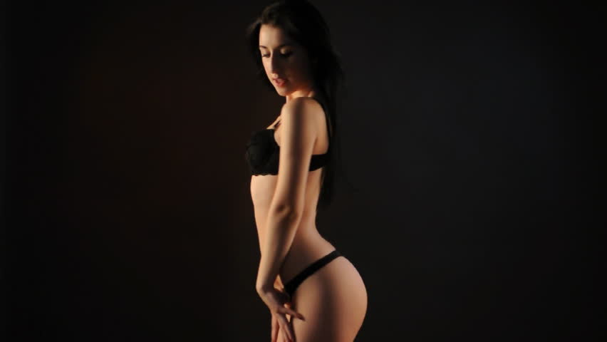 Sexy brunette in black lingerie dancing in the dark. Medium long shot.
