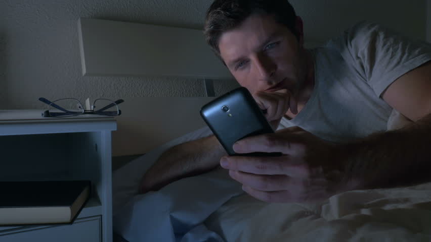 young attractive man with blue eyes lying in bed using mobile phone at bedroom in dim light texting in smartphone and internet social network addiction concept  Royalty-Free Stock Footage #12893597