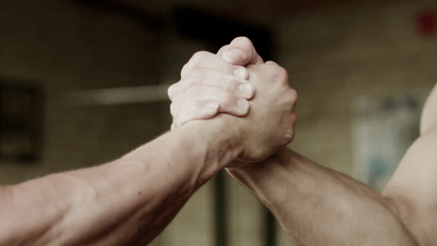 Closeup shot of two strong men having firm handshake after training in gym