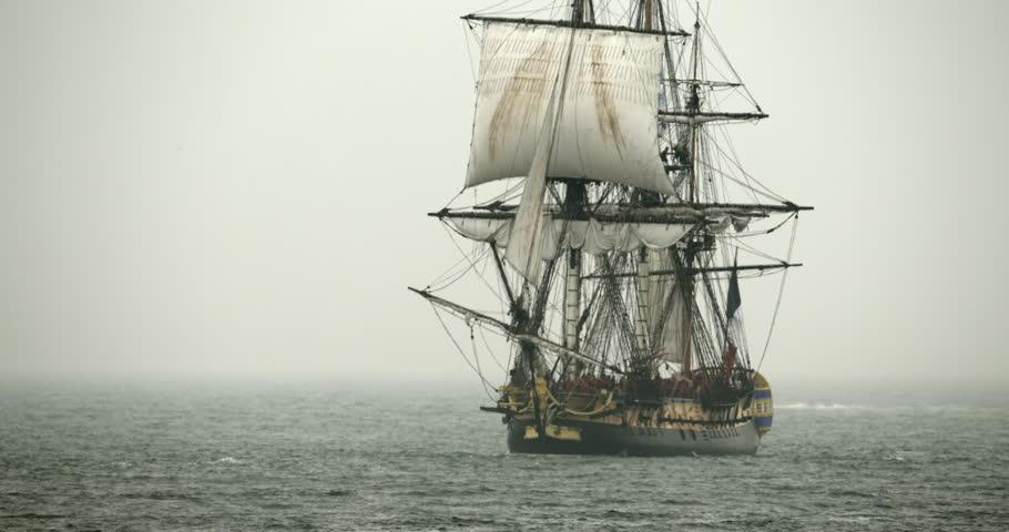 A tall sailing ship schooner sails on the high seas in misty fog.