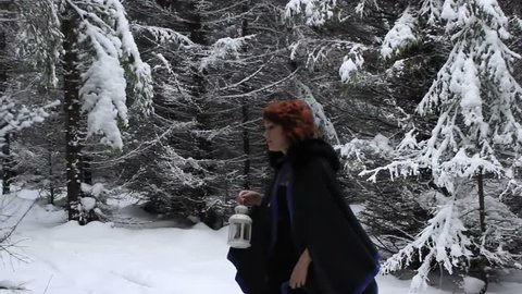 Beautiful girl goes on a footpath in a gloomy winter forest