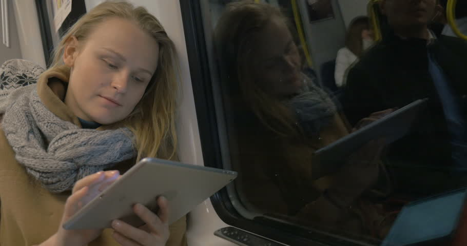 Young woman is sitting in metro train and chatting with friends using tablet PC. | Shutterstock HD Video #12903335