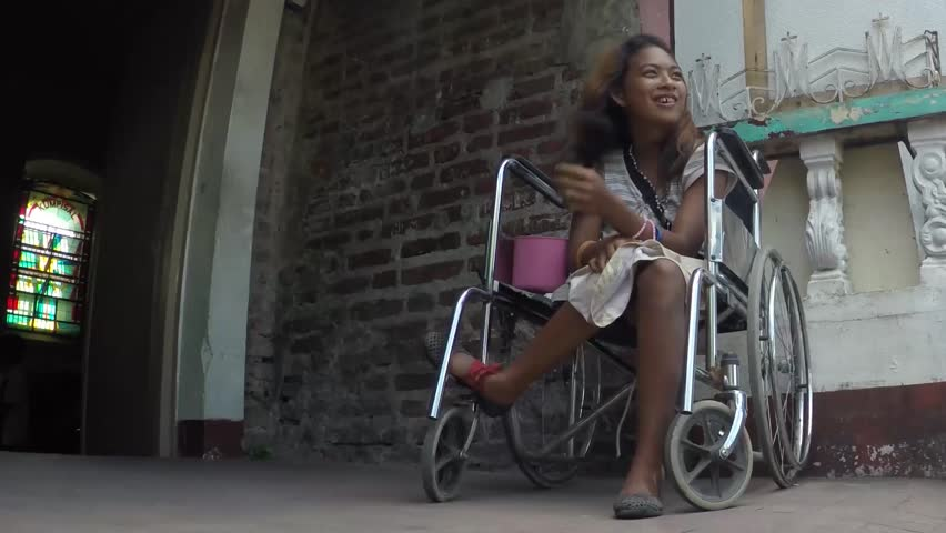 SAN PABLO CITY, LAGUNA, PHILIPPINES - NOVEMBER 21, 2015: A disabled young lady in wheelchair begs at church portal. | Shutterstock HD Video #12910313