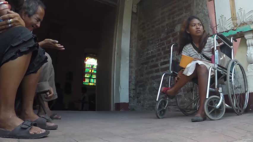 SAN PABLO CITY, LAGUNA, PHILIPPINES - NOVEMBER 21, 2015: A disabled young lady in wheelchair begs at church portal. | Shutterstock HD Video #12910322