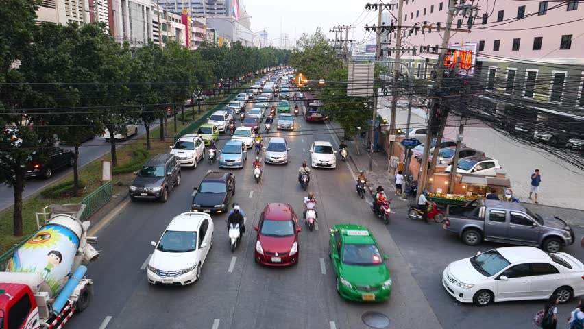 BANGKOK - MARCH 26, 2015: Busy multi-lane city road from above, long slide shot in dusk, footage includes original noises of the city. Ratchadaphisek road at Ratchadaphisek 7 alley intersection