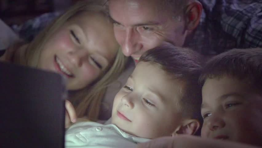 Happy family- Father, mother and Two kids lying down on the sofa and using tablet pc at night. Family watching movie on tablet computer in a dark room. HD 1080p, slow motion 240 fps, high speed camera | Shutterstock HD Video #12912122