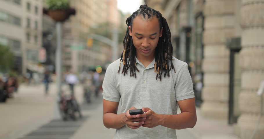 Young man walking New York City street texting cell phone #12917282