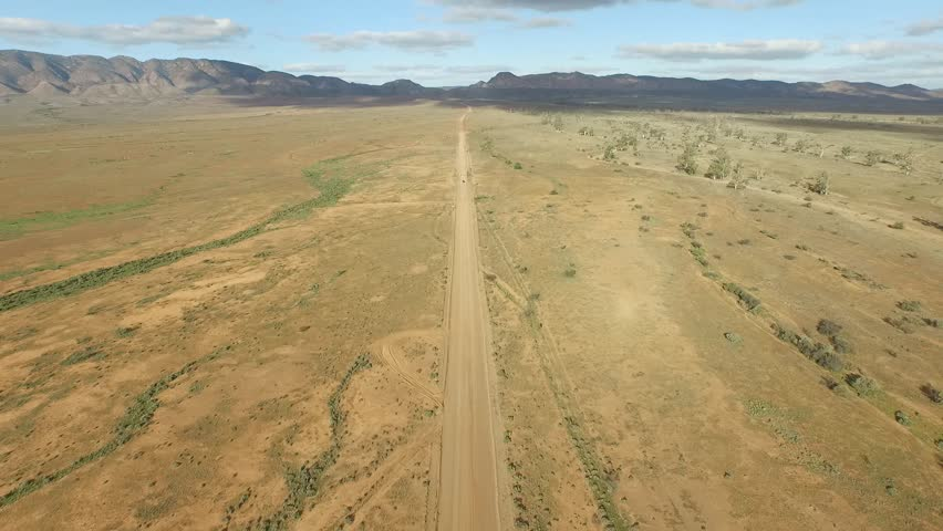 Aerial view of RV vehicle (car) traveling off road on dusty outback Australia country rural Australian dirt track toward mountain ranges. Cruising on open highway toward distant mountains