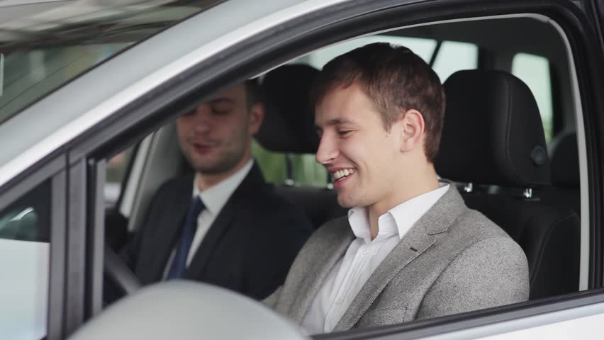 Young man and car seller takling in the car | Shutterstock HD Video #12929648