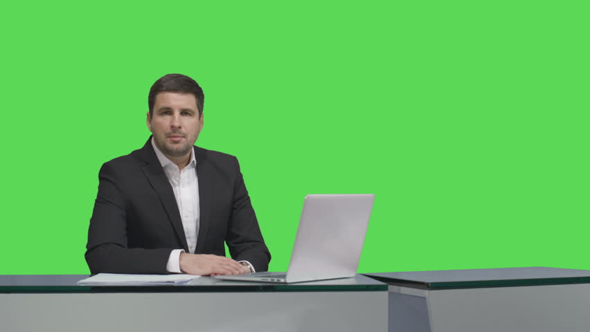 Media broadcaster is sitting at a table and talking on a mock-up green screen in the background. Shot on RED Cinema Camera in 4K (UHD).