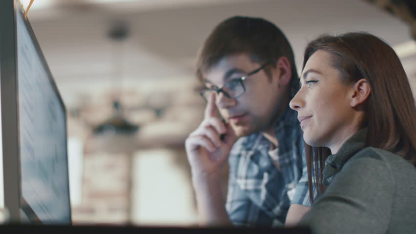 Young man and woman are working on a computer in a loft while discussing a project. Shot on RED Cinema Camera in 4K (UHD). | Shutterstock HD Video #12943253