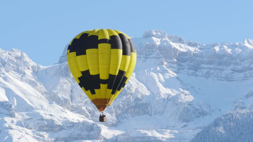 black and yellow balloon with the snowy mountain at the back