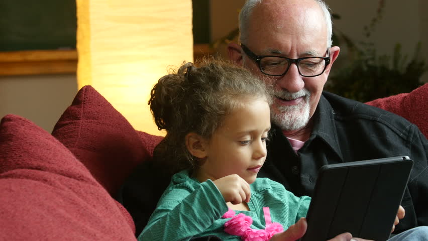 Grandfather sharing an ipad/tablet with his little granddaughter