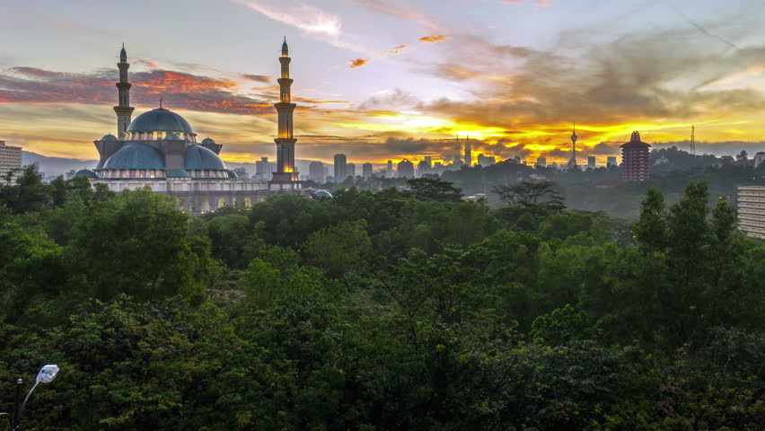 Time lapse. Sunrise at Federal Mosque, Kuala Lumpur with silhouette Kuala Lumpur city skyline. Tilt up. | Shutterstock HD Video #12985280