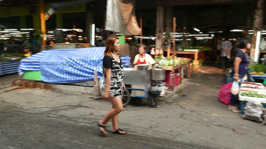 BANGKOK - MARCH 22, 2015: Unidentified stout woman walks against Thai market area, sneeze once, tracking shot with original sound. Iamcharoen market area, under Samrong Bridge viaduct, Sukhumvit road