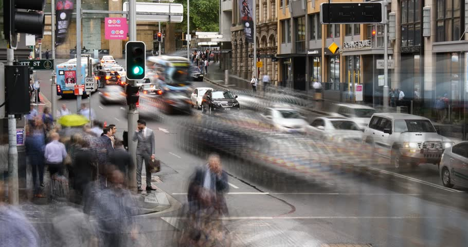 SYDNEY, AUSTRALIA - NOVEMBER 2015: Sydney CBD city street establishing shot with busy peak hour traffic and pedestrian crowd people crossing road time lapse footage with slow shutter effect.
