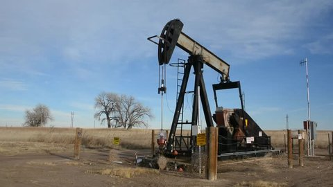 Active Oil Pump Bobbing Donkey Pumpjack in a Field on the Prairie