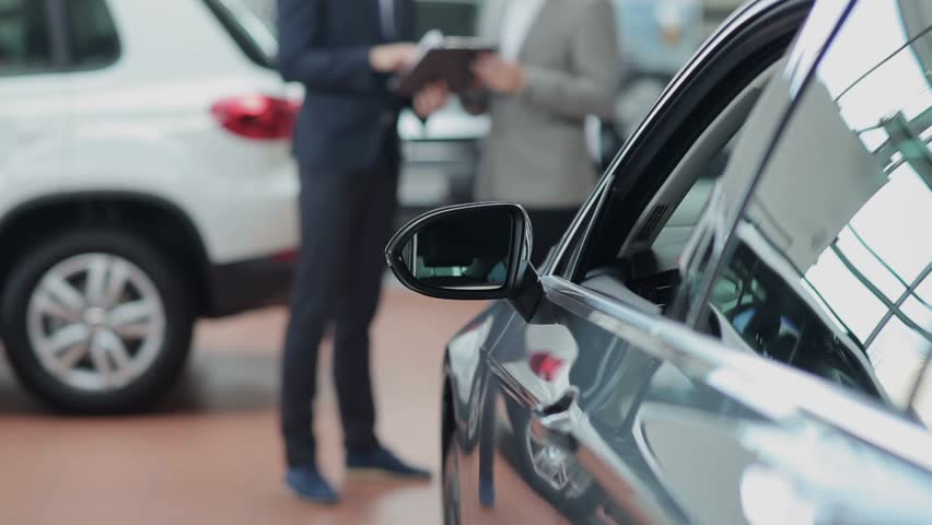 Blurred customer and seller behind a car in motor show | Shutterstock HD Video #13048151