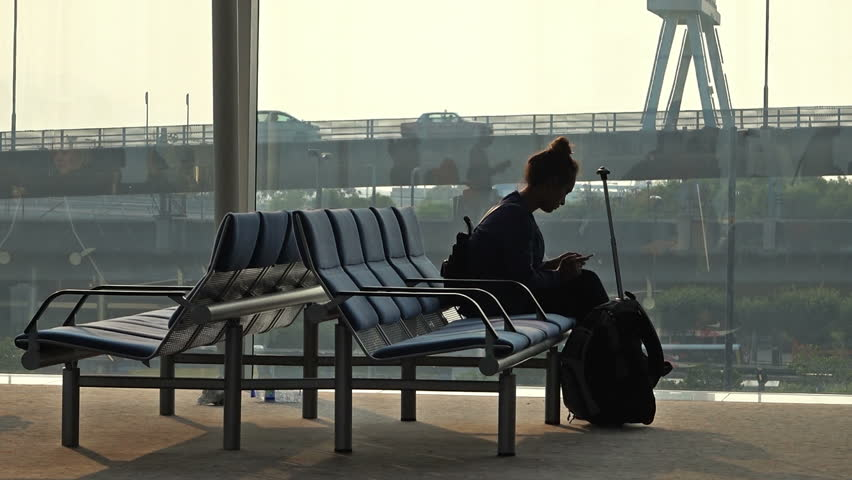 Female traveler waiting for departure and using her cellphone.