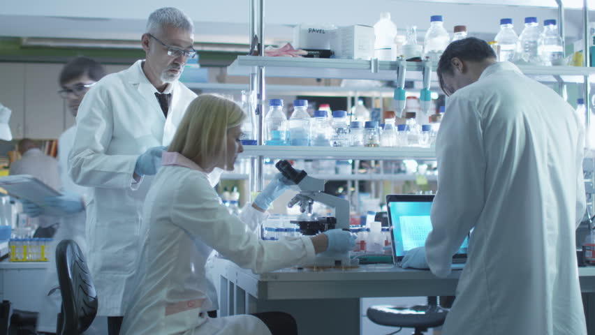 Team of scientists in white coats are working with a laptop and tablet in a laboratory. Shot on RED Cinema Camera in 4K (UHD). | Shutterstock HD Video #13066484