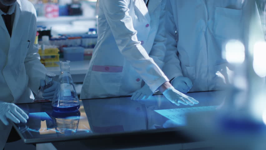 Team of scientists are working on a digital touch screen in a laboratory. Shot on RED Cinema Camera in 4K (UHD). | Shutterstock HD Video #13066649