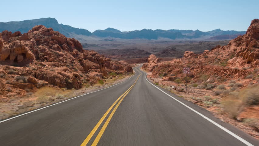 Driving USA: spectacular red rocks and mountains car point of view on lonely empty highway road in Valley of Fire, Nevada desert