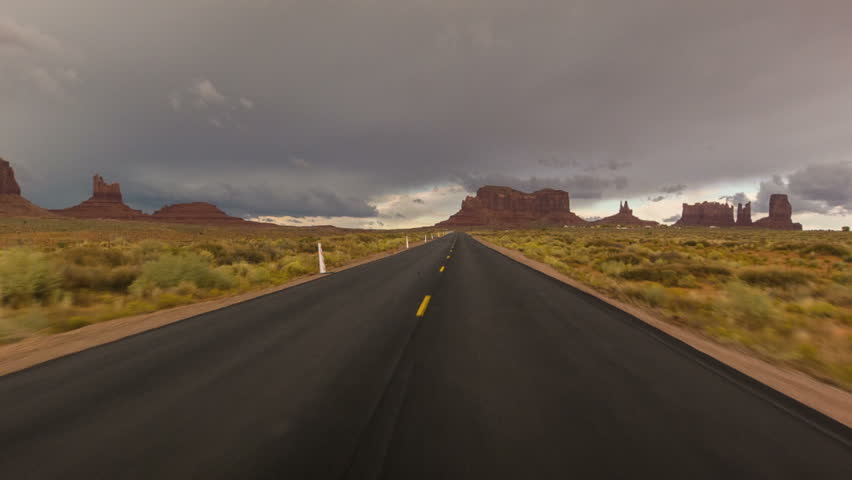 Driving USA: Dramatic point of view POV shot of empty lonely road and stormy skies over Monument Valley, Arizona Utah