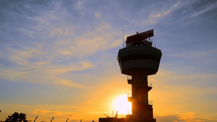 Air traffic control tower with airplane in sunset.