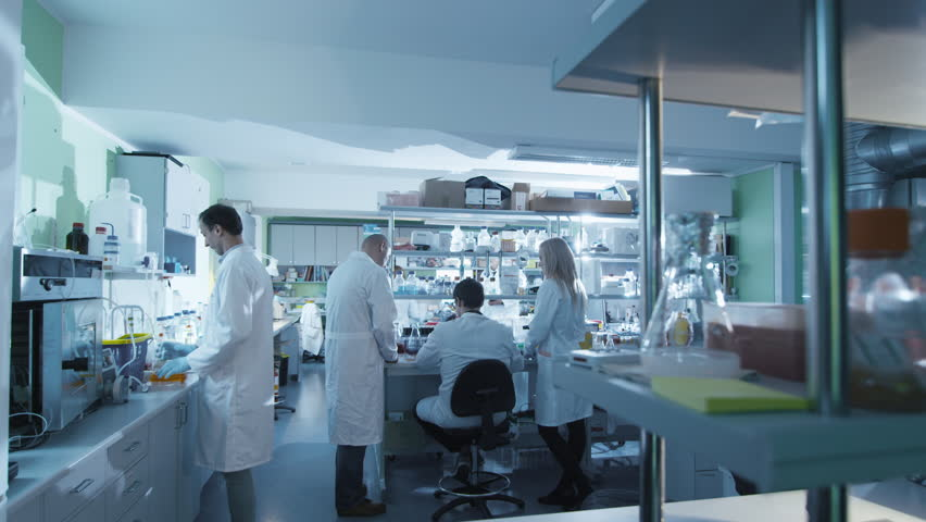 Timelapse  of a team of scientists in white coats that are working in a modern laboratory. Time Lapse of the Team of Brilliant Medical Researches Working on Vaccine Development. Heroes of our Time