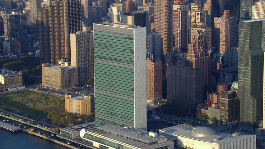 Aerial establishing shot of the United Nations Building in midtown Manhattan, New York City (2015). World leaders meet to discuss peace at the general assembly.