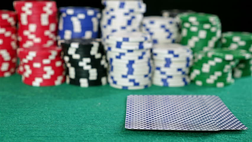 A gambler at a poker table peeks at his cards and bets a stack of chips | Shutterstock HD Video #13105742