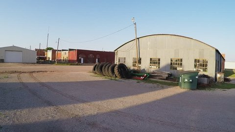 CROWELL, TX/USA - August 3, 2015: Shot of a mid-western farm town dirt back alley. Giant tractor tires are lined up in a row behind an old metal building.