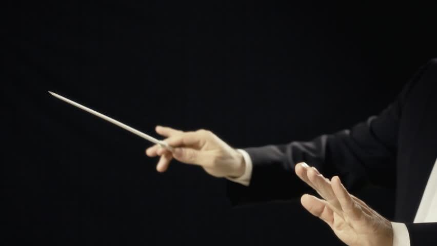 The moving hands of an orchestra conductor directing the musicians. Close-up shot. Conducting: directing a musical performance with visible gestures.