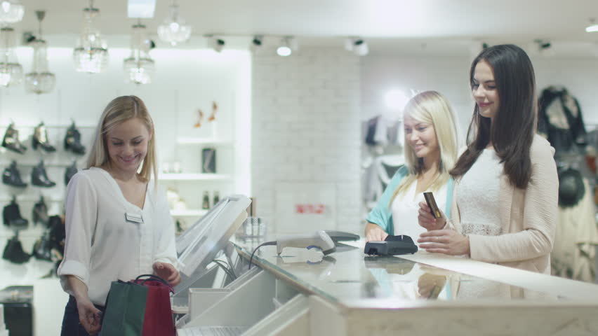 Two cheerful young girls are buying clothes at a cash desk in a department store. Shot on RED Cinema Camera in 4K (UHD).