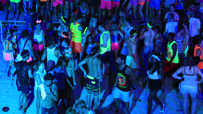 PHANGAN, THAILAND - JANUARY 5, 2015 : Unidentified people participate in the Full Moon party on island Koh Phangan. The event now attracts anywhere from 40,000 party-goers on a normal month | Shutterstock HD Video #13127039