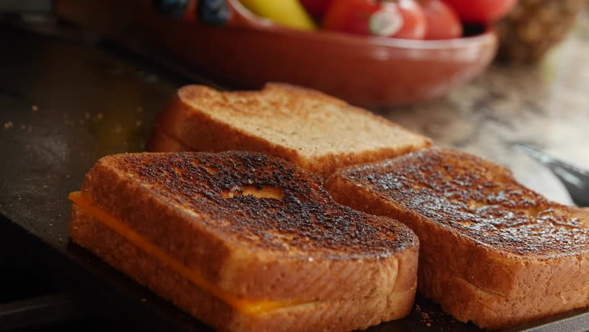 A dolly shot of a woman making gilled cheese sandwiches in the kitchen for lunch | Shutterstock HD Video #13144907